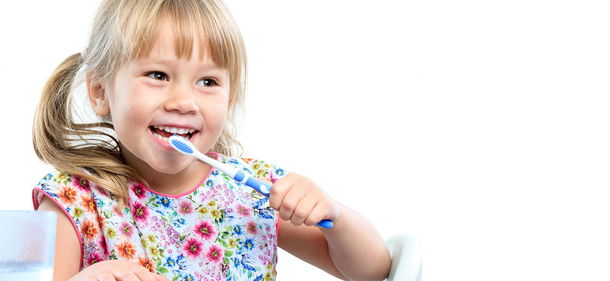 smiling young girl with pigtails brushes her teeth in a flower print dress
