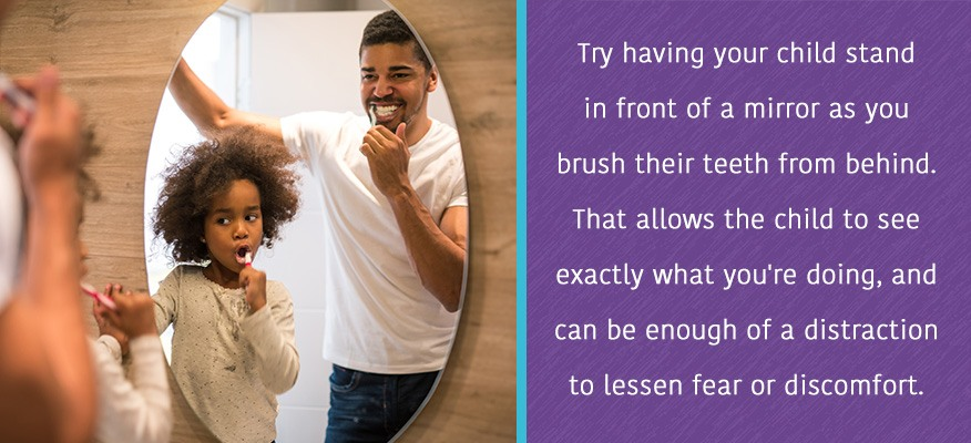 Try having your child stand in front of a mirror as you brush their teeth from behind.