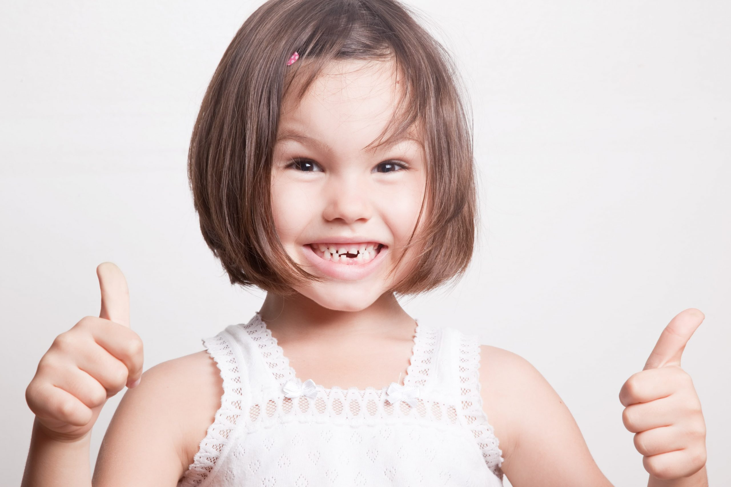 little girl with missing front teeth smiles with two thumbs up